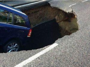 Araba, dev çukurun ucunda asılı kaldı