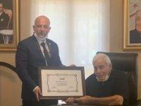 İŞAD, Mustafa Hacı Ali'ye onursal üyelik şilti takdim etti