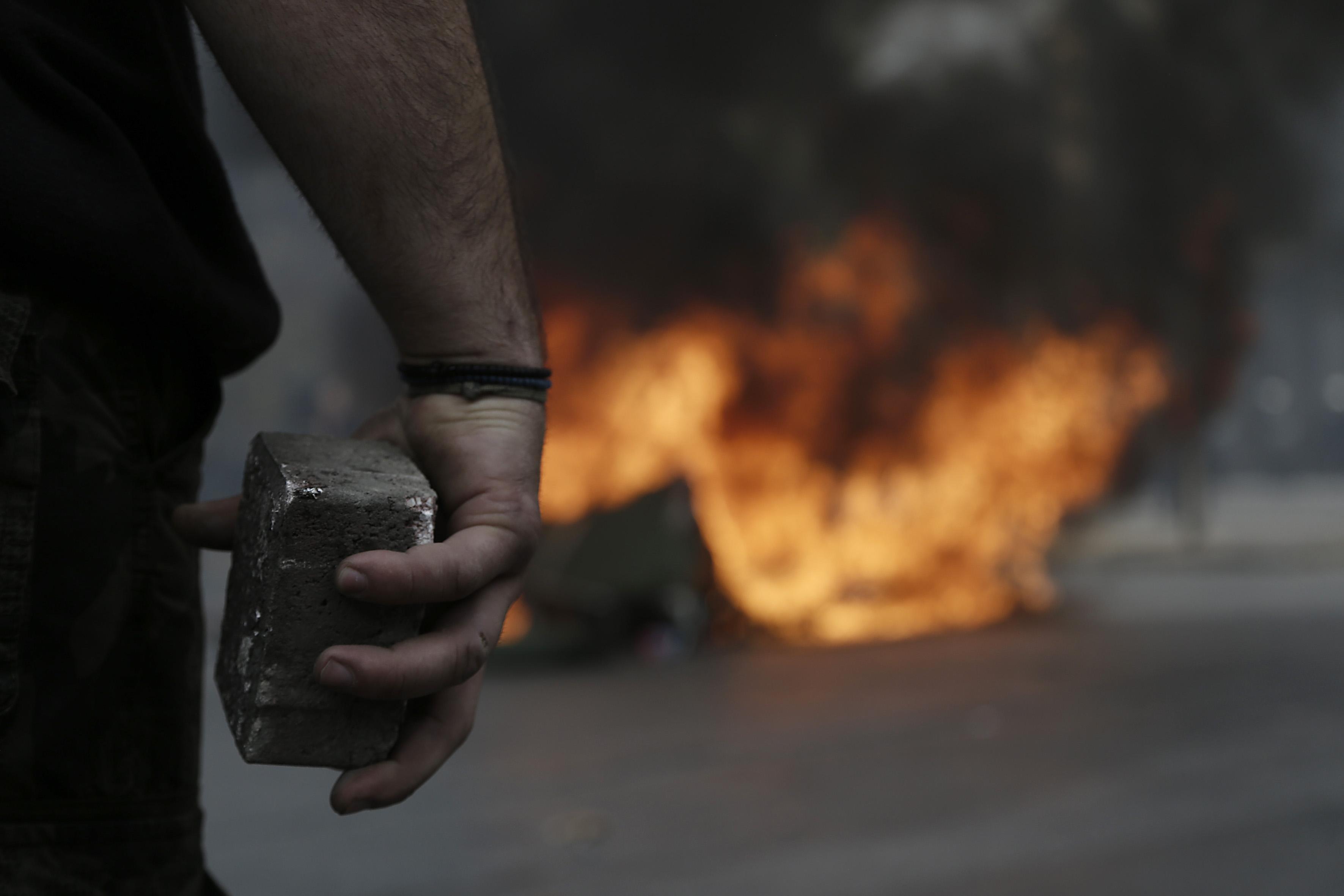 Ένας αγρότης από την Κρήτη που έχει φθάσει από το λιμάνι του Πειραιά κρατάει μια πέτρα κατά την διάρκεια επεισοδίων έξω από το υπουργείο Αγροτικής Ανάπτυξης, Παρασκευή 12 Φεβρουαρίου 2016. Αγρότες από μπλόκα από όλη την Ελλάδα έχουν προγραμματίσει διήμερη διαμαρτυρία στο Σύνταγμα ζητώντας την απόσυρση του σχεδίου για το ασφαλιστικό, την κατάργηση της φορολόγησης από το πρώτο ευρώ, την κατάργηση του ειδικού φόρου κατανάλωσης στο κρασί καθώς και την καθιέρωση αφορολόγητου πετρελαίου. ΑΠΕ-ΜΠΕ/ΑΠΕ-ΜΠΕ/ΓΙΑΝΝΗΣ ΚΟΛΕΣΙΔΗΣ